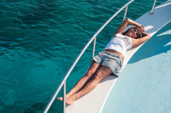 Brunette woman laying on shipboard of yacht. Happy brunette female laying on shipboard of yacht. Copyspace Stock Photography