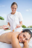 Happy brunette getting a honey beauty treatment poolside Royalty Free Stock Images