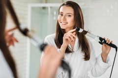 Happy brunette girl in bathrobe using hair curler at mirror. In bathroom stock photography