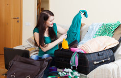 Happy brunette girl choosing dress for vacation Stock Photo