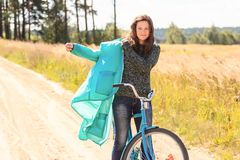 Happy brunette girl at cycling on dirt road Royalty Free Stock Photo