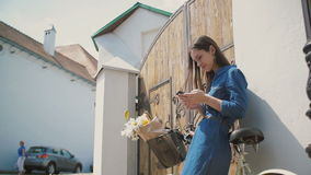 Happy brunette girl laughing and talking on the phone with a bike and flowers in a basket, using her smartphone, slow mo stock footage