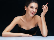 Happy brunette girl with lipstick on black background. royalty free stock photos