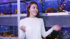 Happy brunette girl looking at tropical fish stock footage