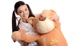 Happy brunette girl playing with a big teddy bear. Royalty Free Stock Image