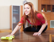 Happy brunette girl wiping the dust. From wooden furniture at home Royalty Free Stock Photography
