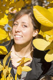 Happy brunette girl among yellow autumn leaves Royalty Free Stock Photos