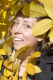 Happy brunette girl among yellow autumn leaves Royalty Free Stock Photo
