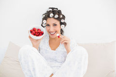 Happy brunette in hair rollers having a bowl of strawberries Royalty Free Stock Image