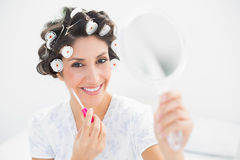 Happy brunette in hair rollers holding hand mirror and lip gloss Royalty Free Stock Images