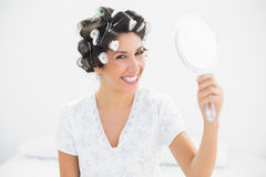 Happy brunette in hair rollers holding hand mirror smiling at ca. Mera at home in bedroom Royalty Free Stock Photography