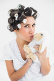 Happy brunette in hair rollers kissing sheep teddy Royalty Free Stock Images