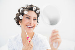 Happy brunette in hair rollers looking in hand mirror and holding  lip gloss Stock Images