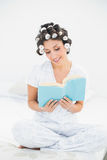 Happy brunette in hair rollers reading a book on bed Royalty Free Stock Image