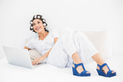 Happy brunette in hair rollers and wedge shoes using her laptop Stock Photo