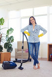 Happy brunette having finished cleaning of carpet. Mid shot of gorgeous woman cleaning with vacuum cleaner carpet royalty free stock photography