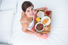 Happy brunette having her breakfast in bed Royalty Free Stock Photo
