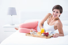 Happy brunette having her breakfast in bed Royalty Free Stock Photography