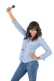 Happy brunette with her hand on hip holding microphone Stock Photos