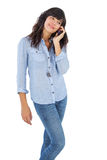 Happy brunette with her mobile phone calling someone Royalty Free Stock Photo