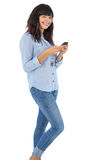 Happy brunette with her mobile phone texting a message Royalty Free Stock Image