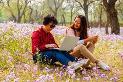 Smiling daughter showing laptop computer to mother while sitting in a park. royalty free stock images