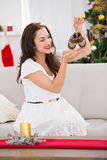 Happy brunette holding baby shoes at christmas Royalty Free Stock Photography