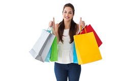Happy brunette holding bags with thumbs up Stock Photo