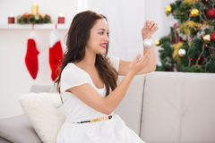 Happy brunette holding a bauble at christmas Royalty Free Stock Photos