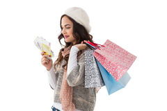 Happy brunette holding cash and shopping bags Royalty Free Stock Photo