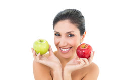 Happy brunette holding red and green apples and looking at camer Stock Image