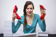 Happy brunette holding up red shoes Royalty Free Stock Photography