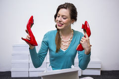 Happy brunette holding up red shoes Royalty Free Stock Photo