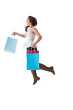 Happy brunette leaping with shopping bags Stock Images