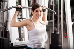 Happy brunette lifting weights Royalty Free Stock Photography