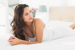 Happy brunette lying on bed. At home in bedroom Royalty Free Stock Images