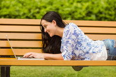 Happy brunette lying on bench using laptop Royalty Free Stock Photography