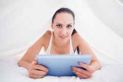 Happy brunette lying under the sheets holding her tablet pc Royalty Free Stock Photography