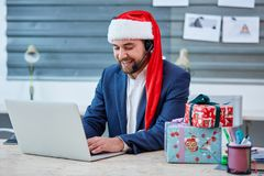Male office worker wearing a Christmas hat, a suit and headphones on head, sits at desk and uses a laptop. stock photos