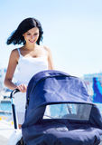 Happy brunette mother walking with the baby outdoors Royalty Free Stock Images