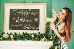 Happy brunette posing by the fireplace on camera Christmas photo shoot royalty free stock image
