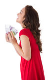 Happy brunette in red dress holding cash Royalty Free Stock Image
