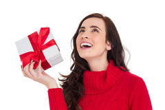 Happy brunette in red jumper hat showing a gift Stock Photography