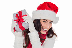 Happy brunette in santa hat holding gift Stock Photography