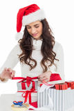 Happy brunette in santa hat packing gifts Stock Photos