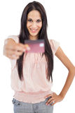 Happy brunette showing her credit card to camera Royalty Free Stock Image