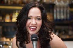 Happy brunette singing into mic Stock Photo