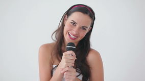 Happy brunette singing into a microphone stock video footage