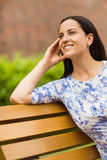Happy brunette sitting on bench relaxing Stock Image