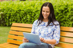 Happy brunette sitting on bench using tablet Stock Images